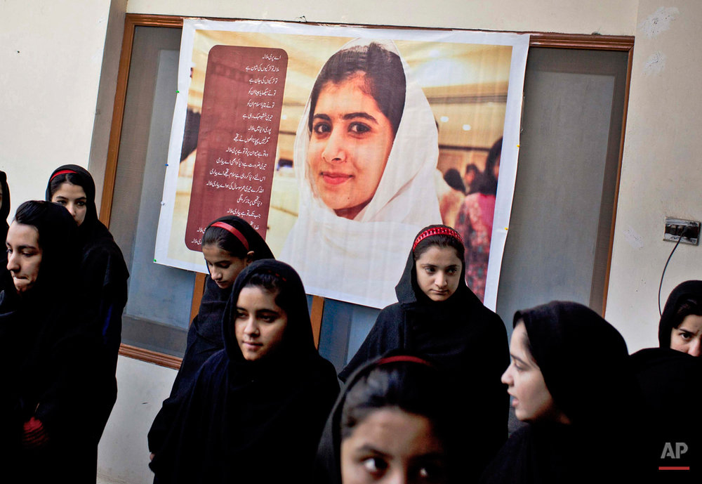 In this Thursday, Nov. 15, 2012 photo, Pakistani girls gather under a poster of Malala Yousufzai in her old school in Mingora, Swat Valley, Pakistan. Taliban attack survivor Malala Yousafzai of Pakistan won the Nobel Peace Prize on Friday, Oct. 10, 2014, for risking their lives to fight for children's rights. Malala, who moved to Britain for treatment and later settled there, tirelessly continued her campaign for a woman's right to an education in Pakistan and won international recognition for her struggle. But in Pakistan that effort has not stopped as young girls and women struggle to get an education. (AP Photo/Anja Niedringhaus)