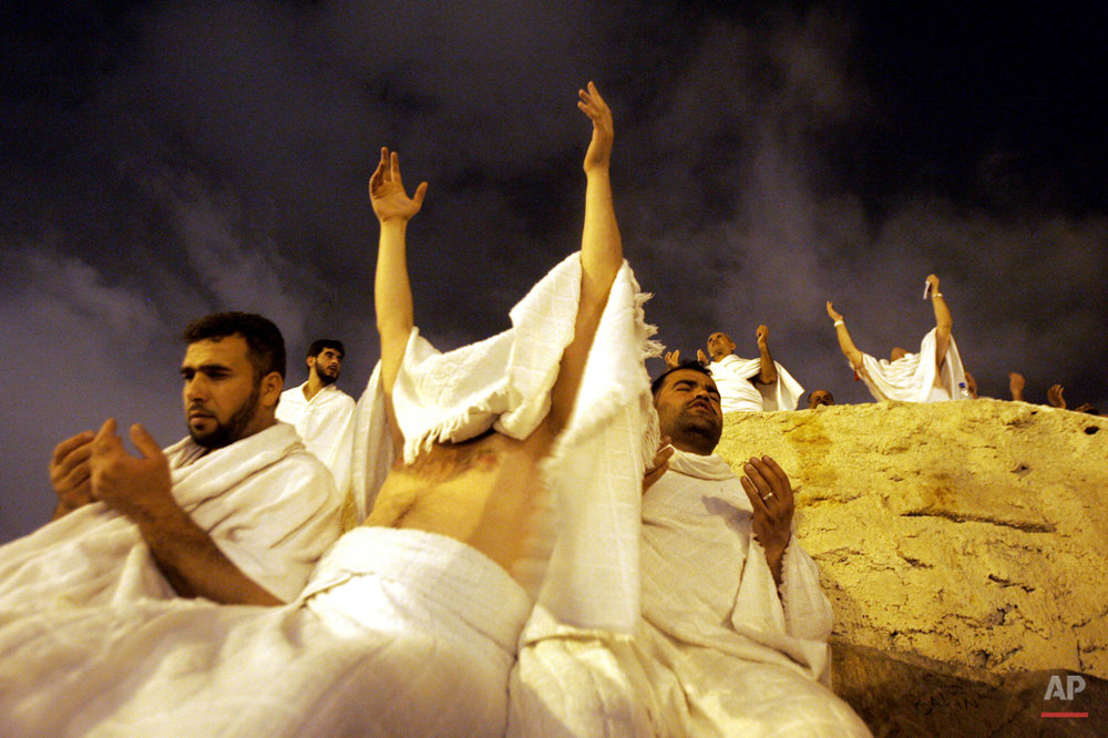 Muslim pilgrims pray at Jabal Al Rahma holy mountain, the mountain of forgiveness, in Arafat outside Mecca, Saudi Arabia early Monday, Jan. 9, 2006. At least 2.5 million pilgrims attended the hajj. The hajj is required at least once in the lifetime of every able-bodied Muslim who can afford it. Muslims believe completing the hajj will erase their sins. (AP Photo/Muhammed Muheisen)
