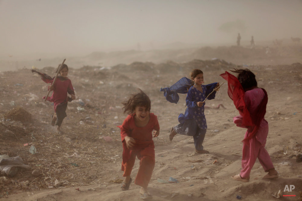 Pakistani girls react as they get caught in a sand storm, in a slum on the outskirts of Islamabad, Pakistan, Wednesday, May 25, 2011. (AP Photo/Muhammed Muheisen)