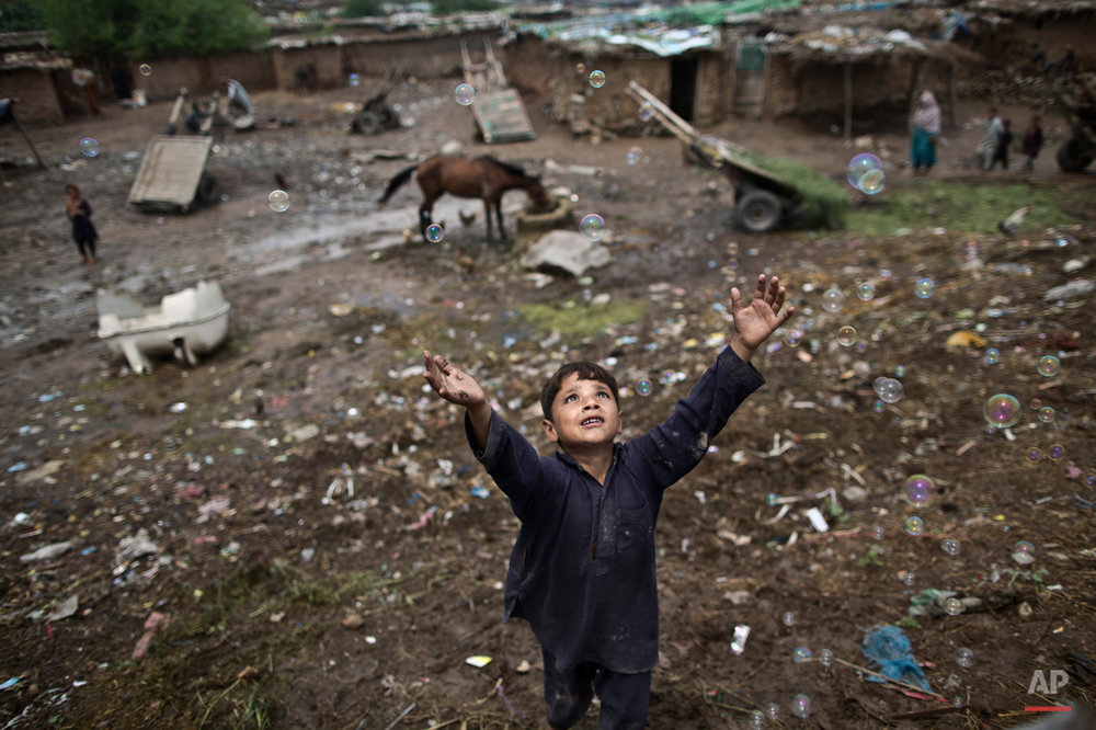 An Afghan refugee child, chases bubbles released by other children, while playing on the outskirts of Islamabad, Pakistan, Friday, Aug. 8, 2014. For more than three decades, Pakistan has been home to one of the world's largest refugee communities: hundreds of thousands of Afghans who have fled the repeated wars and fighting in their country. Since the 2002 U.S.-led invasion of Afghanistan some 3.8 million Afghans have returned to their home country, according to the U.N.'s refugee agency, but thousands of others still live without electricity, running water and other basic services. (AP Photo/Muhammed Muheisen)