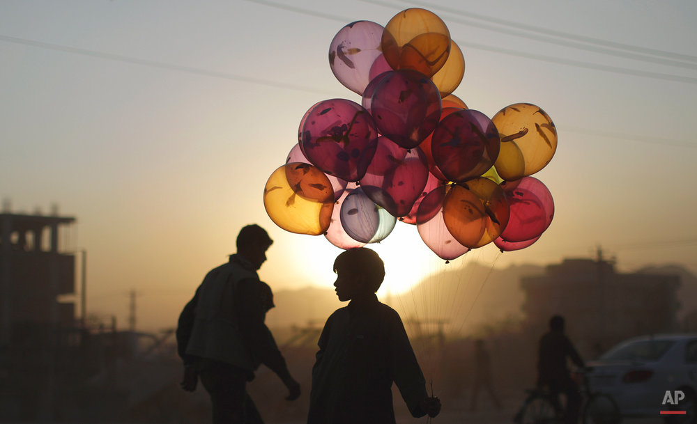 Afghan boy Mahfouz Bahbah, 12, stands on a roadside hoping to sell his balloons during sunset  in Kabul, Afghanistan, Tuesday, Oct. 18, 2011. (AP Photo/Muhammed Muheisen)