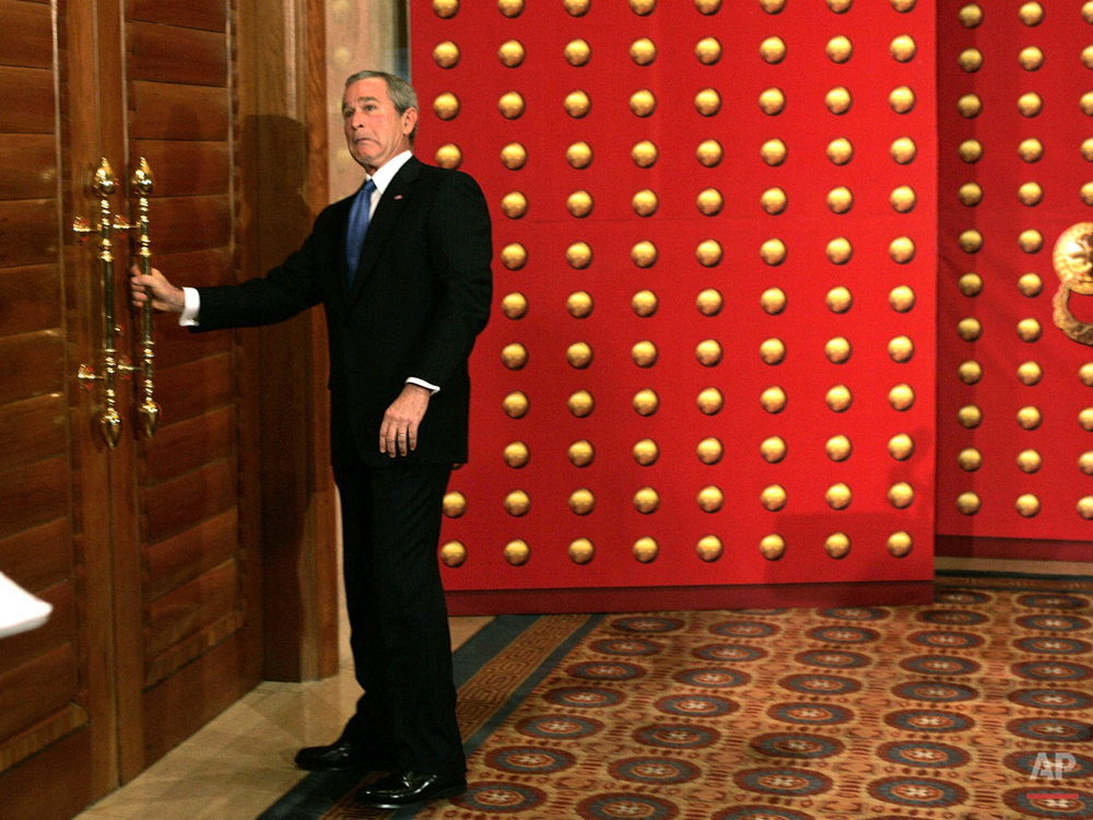 U.S. President George W. Bush reacts as he pulls on a locked door as he tries to leave a press conference in Beijing, China, Sunday, Nov. 20, 2005. Bush headed for a set of double doors after the press conference only to discover that they were locked. (AP Photo/Charles Dharapak)