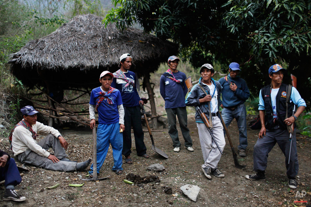 In this Sept. 4, 2014 photo, Belen Chapi Civil Defense Committee members arrive after walking five hours from their village to assist in an exhumation of mass graves with the bodies of villagers slain by security forces, in Paccha village of Peru. Before the 1984 massacre, the hamlet was a refuge for dozens of families trying to flee the conflict, said sole survivor Dolores Guzman, who was 20 years old and four months pregnant at the time. (AP Photo/Rodrigo Abd)
