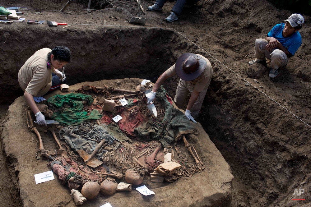 In this Sept. 6, 2014 photo, Eusebio Cuadros, right, watches as forensic anthropologists Soldad Mostacero, left, and Osvaldo Calcina, center right, exhume a mass grave of people slain by security forces, in the Paccha village, in the district of Chungui, Peru. Cuadros' aunt, Natividad, was one of the villagers slain in the July 14, 1984 massacre in Paccha, a hamlet located in the Andean slopes beside the Apurimac river where government forces regularly hunted alleged collaborators of the Maoist guerrillas. (AP Photo/Rodrigo Abd)