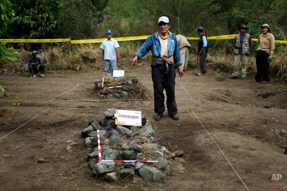 In this Sept. 4, 2014 photo, Felix Casa, right center, and Cipriano Huaman, back left, pose for the visual anthropologist, pointing to the graves where they believe their relatives were buried during an exhumation of mass graves of villagers slain by security forces, in the Paccha village of Chungui, Peru. In all, 21 sets of human remains were recovered, including those of eight children and a fetus, said Luis Rueda, the forensic archaeologist overseeing the dig. (AP Photo/Rodrigo Abd)