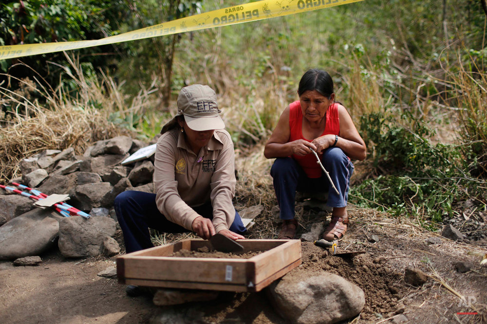 In this Sept. 4, 2014 photo, Severina Osco observes how forensic photographer Angela Inostroza looks for bone fragments in the soil removed in an exhumation of mass graves of villagers slain by security forces in 1984, in the Paccha village of Peru. Osco is trying to locate the body of her sister, Natilda, who disappeared in 1984. (AP Photo/Rodrigo Abd)