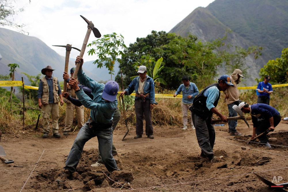 In this Sept. 4, 2014 photo, Belen Chapi Civil Defense Committee members begin digging an area mapped by forensic anthropologists in an exhumation of mass graves of villagers slain by security forces, in the Paccha village of Chungui, Peru. The exhumation was part of an effort by the Peruvian government to find out more about the human rights violations committed during the 1980-2000 internal conflict, and try to identify those who were responsible. (AP Photo/Rodrigo Abd)