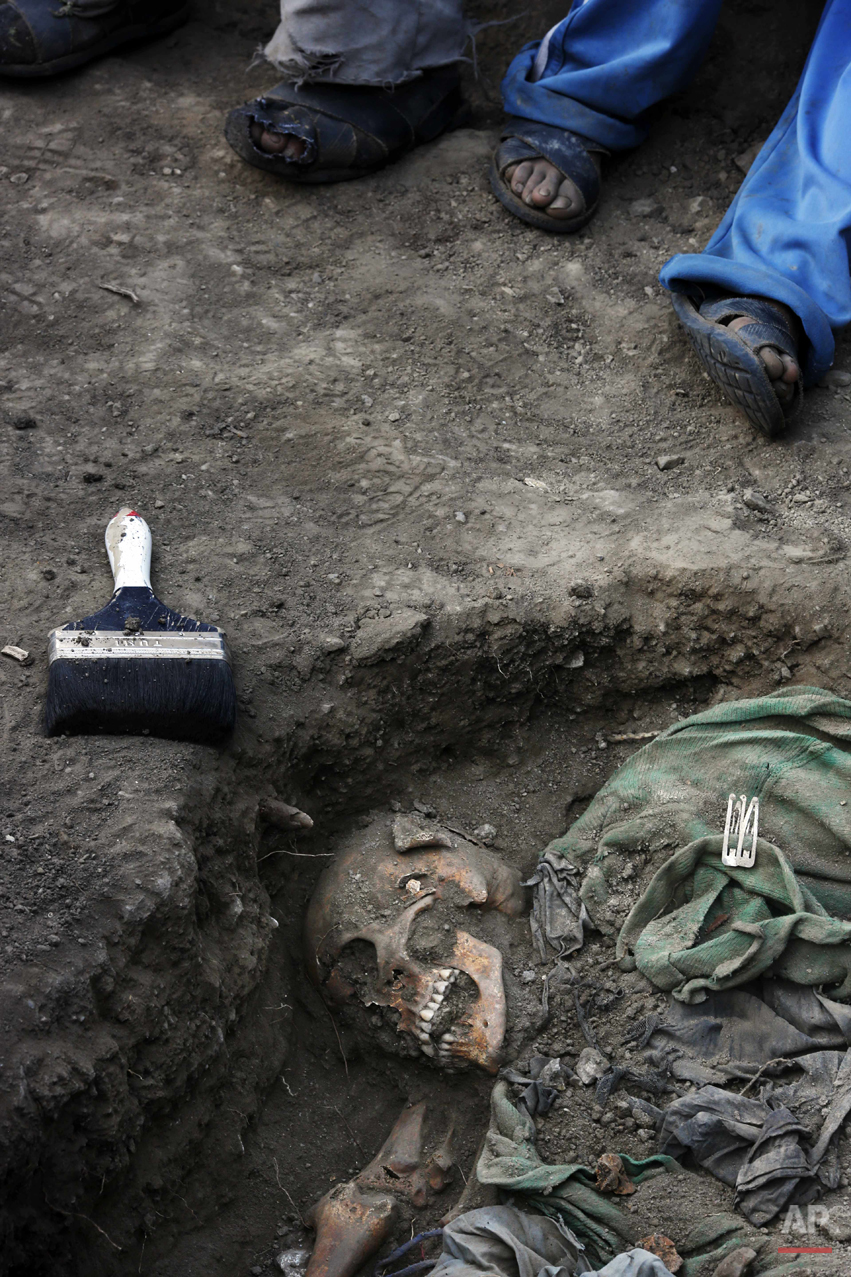 In this Sept. 4, 2014 photo, villagers hired by forensic anthropologists take a break from helping the exhumation of mass graves of people slain by government security forces in 1984, in the Paccha village of Peru. After more than a week of digging, forensic anthropologists reported three mass graves were found, from which 21 sets of human remains were recovered, including eight children and a fetus. (AP Photo/Rodrigo Abd)