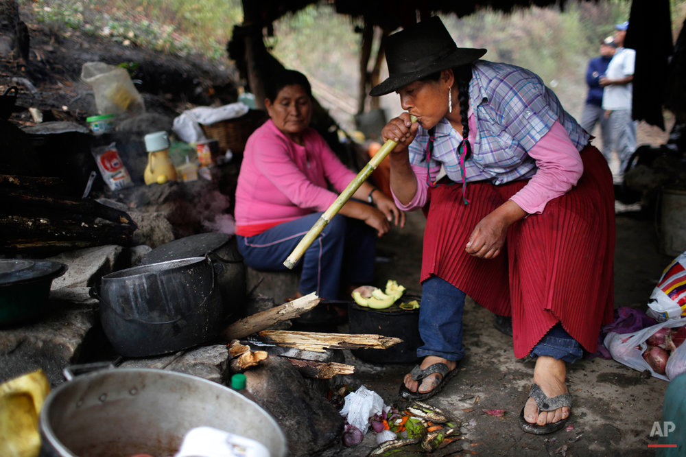 In this Sept. 5, 2014 photo, Dolores Guzman blows into a cane reed to stoke a fire at a makeshift camp in the Paccha village of Peru. Guzman, sole survivor of the Paccha massacre, journeyed from Lima to help forensic investigators find the common graves of the people slain by government security forces in 1984. Before the massacre, the hamlet was a refuge for dozens of families trying to flee the conflict, said Guzman, who was 20 years old and four months pregnant at the time. (AP Photo/Rodrigo Abd)