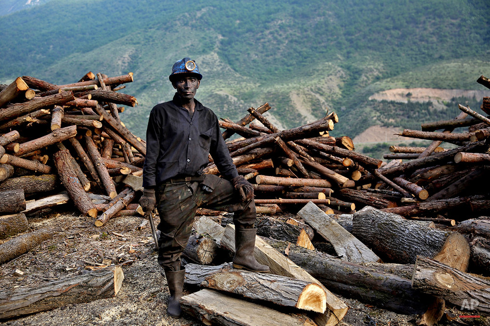 In this Wednesday, May 7, 2014 photo, an Iranian coal miner stops collecting logs to pose for a photograph at a mine  on a mountain in Mazandaran province, near the city of Zirab, 212 kilometers (132 miles) northeast of the capital Tehran, Iran. The workers make just $300 a month, little more than minimum wage. (AP Photo/Ebrahim Noroozi)