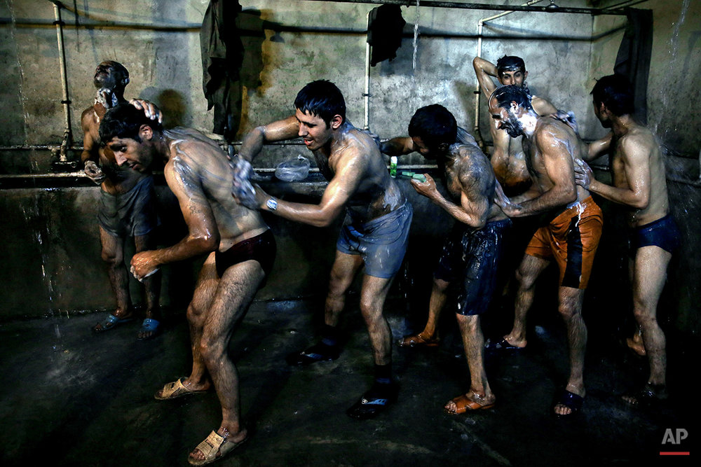 In this Tuesday, May 6, 2014 photo, Iranian coal miners shower after a long day of work at a mine on a mountain in Mazandaran province, near the city of Zirab, 212 kilometers (132 miles) northeast of the capital Tehran, Iran. Workers who put in 12 hours a day - often in dangerous conditions - make just $300 a month. (AP Photo/Ebrahim Noroozi)