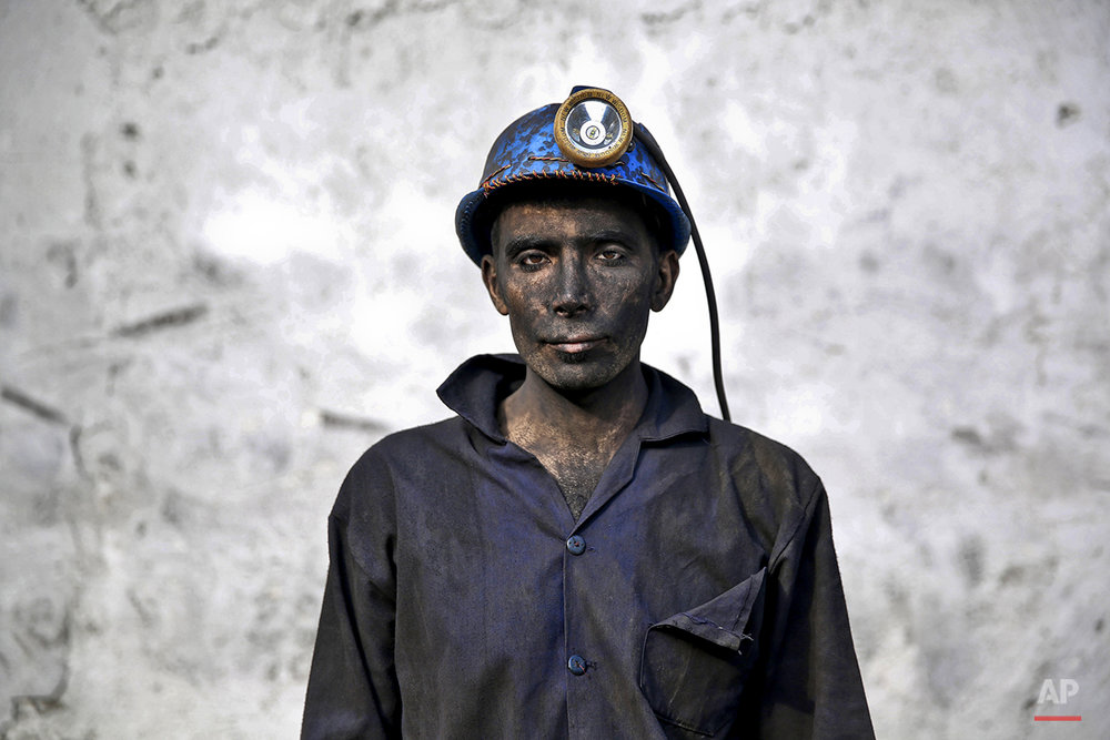 In this Wednesday, May 7, 2014 photo, an Iranian coal miner with his face smeared black from coal poses for a photograph at a mine near the city of Zirab 212 kilometers (132 miles) northeast of the capital Tehran, on a mountain in Mazandaran province, Iran. The workers who put in long hours in often dangerous conditions and make just $300 a month, little more than minimum wage. (AP Photo/Ebrahim Noroozi)