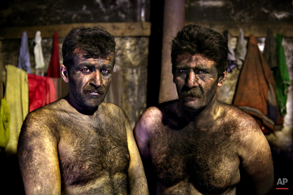 In this Wednesday, May 7, 2014 photo, Iranian coal miners pose for a photograph before taking a shower after a long day of work at a mine on a mountain in Mazandaran province, near the city of Zirab 212 kilometers (132 miles) northeast of the capital Tehran  Iran. The miners put in long hours in often dangerous conditions making just $300 a month, little more than minimum wage. (AP Photo/Ebrahim Noroozi)