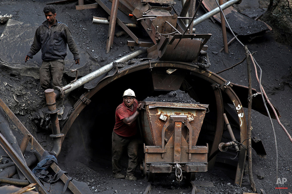 In this Monday, Aug. 18, 2014 photo, an Iranian coal miner pushes a metal cart loaded with coal at a mine near the city of Zirab 212 kilometers (132 miles) northeast of the capital Tehran, on a mountain in Mazandaran province, Iran. The miner move up to 100 tons of coal a day. (AP Photo/Ebrahim Noroozi)