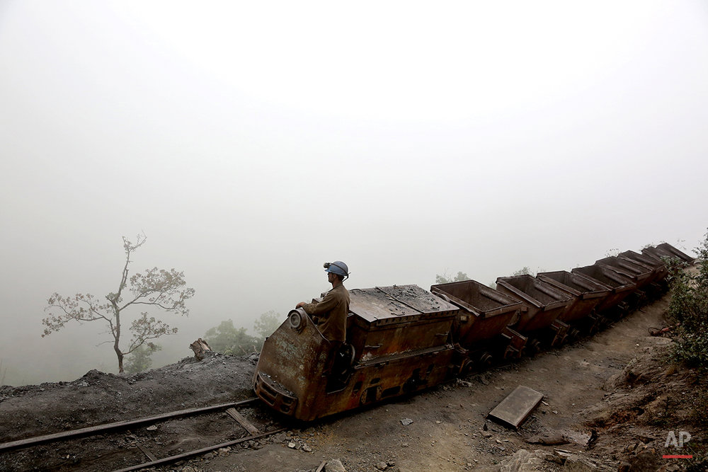 In this Thursday, May 8, 2014 photo, an Iranian coal miner moves wagons to be loaded with coal at a mine near the city of Zirab 212 kilometers (132 miles) northeast of the capital Tehran, on a mountain in Mazandaran province, Iran. International sanctions linked to the decade-long dispute over Iran's nuclear program have hindered the import of heavy machinery and modern technology in all sectors, and coal mining is no exception. (AP Photo/Ebrahim Noroozi)