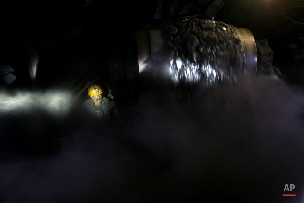 In this Tuesday, Aug. 19, 2014 photo, an Iranian coal miner works inside a mine near the city of Zirab 212 kilometers (132 miles) northeast of the capital Tehran, on a mountain in Mazandaran province, Iran. The miners tunnel deep into the mountains, working in dark, narrow passageways where the risk of toxic gases and cave-ins is never far from their minds. (AP Photo/Ebrahim Noroozi)