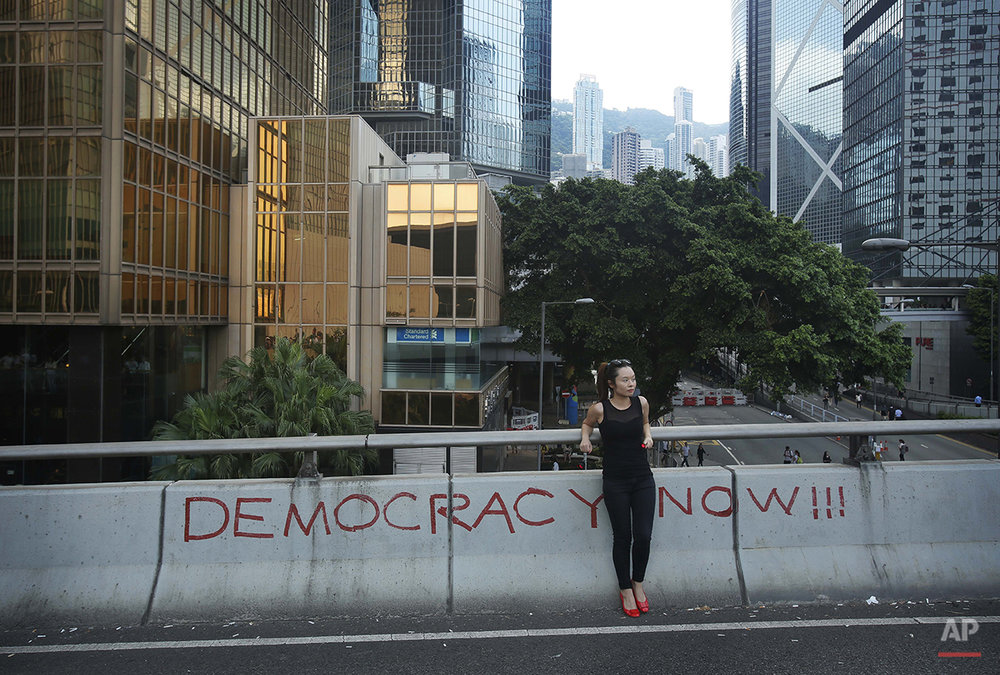 A woman rests on an overpass closed due to a massive protest in Hong Kong, Monday, Sept. 29, 2014. Pro-democracy protesters expanded their rallies throughout Hong Kong on Monday, defying calls to disperse in a major pushback against Beijing's decision to limit democratic reforms in the Asian financial hub. (AP Photo/Wally Santana)