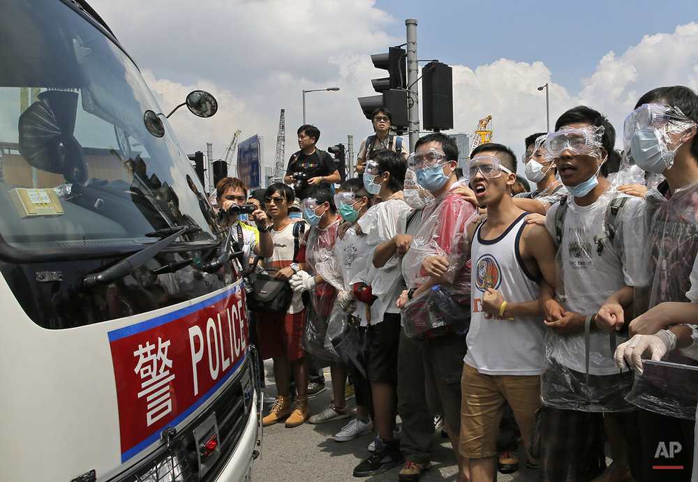 Protesters wear masks and goggles to protect themselves from pepper spray while blocking a police car outside the government headquarters  in Hong Kong, Sunday, Sept. 28, 2014. Hong Kong activists kicked off a long-threatened mass civil disobedience protest Sunday to challenge Beijing over restrictions on voting reforms, escalating the battle for democracy in the former British colony after police arrested dozens of student demonstrators. (AP Photo/Vincent Yu)