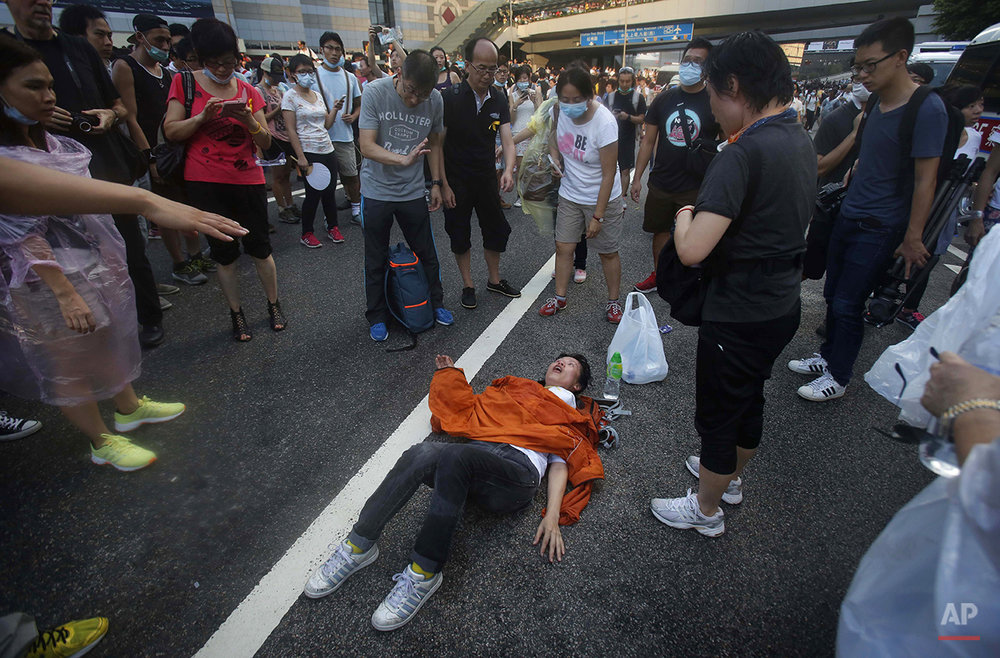 A woman collapses on a street as riot police fire tear gas and pepper spray into the crowds of thousands of protesters surrounding the government headquarters in Hong Kong Sunday, Sept. 28, 2014. Hong Kong police used tear gas on Sunday and warned of further measures as they tried to clear thousands of pro-democracy protesters gathered outside government headquarters in a challenge to Beijing over its decision to restrict democratic reforms for the city. (AP Photo/Wally Santana)