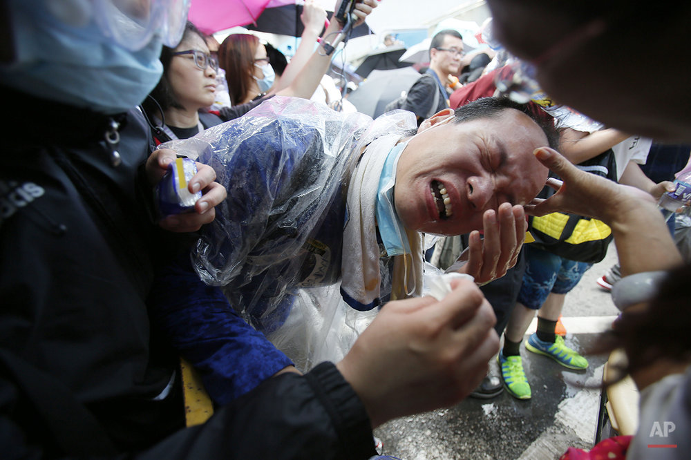 A student protester is overcome by pepper spray from riot police as thousands of protesters surround the government headquarters in Hong Kong Sunday, Sept. 28, 2014. Hong Kong police used tear gas on Sunday and warned of further measures as they tried to clear thousands of pro-democracy protesters gathered outside government headquarters in a challenge to Beijing over its decision to restrict democratic reforms for the city. (AP Photo/Wally Santana)