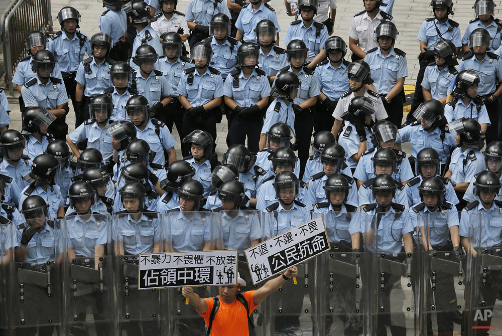 "A protester raises placards that read ""Occupy Central,"" left, and ""Civil disobedience"" in front of riot policemen outside the government headquarter in Hong Kong Saturday, Sept. 27, 2014. Riot police on Saturday arrested scores of students who stormed the government headquarters compound in Hong Kong's Central district during a night of scuffles to protest China's refusal to allow genuine democratic reforms in the semiautonomous region. (AP Photo/Vincent Yu)"