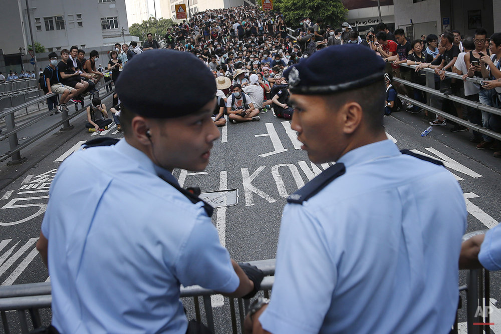 Pro-democracy protesters sit on a road as they face-off with local police, Monday, Sept. 29, 2014 in Hong Kong. Pro-democracy protesters expanded their rallies throughout Hong Kong on Monday, defying calls to disperse in a major pushback against Beijing's decision to limit democratic reforms in the Asian financial hub. (AP Photo/Wong Maye-E)