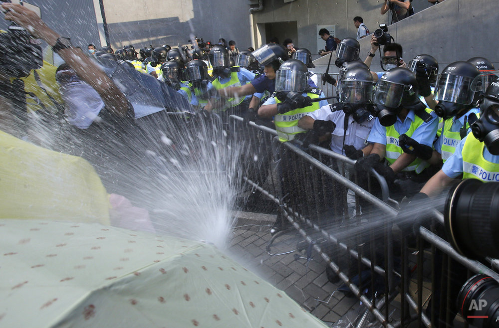 Riot police fire pepper spray on student protesters surrounding the government headquarters in Hong Kong, Sunday, Sept. 28, 2014. Hong Kong police used tear gas on Sunday and warned of further measures as they tried to clear thousands of pro-democracy protesters gathered outside government headquarters in a challenge to Beijing over its decision to restrict democratic reforms for the city. (AP Photo/Wally Santana)