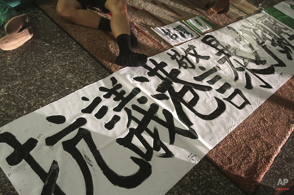 "A student demonstrator supporting pro-democracy protests taking place in Hong Kong sleeps with a banner reading ""Protest Hong Kong Police brutal force"" on the floor as they occupy the first floor of Hong Kong Economic, Trade and Cultural Office in Taipei, Taiwan, early Monday, Sept. 29, 2014. (AP Photo/Chiang Ying-ying)"