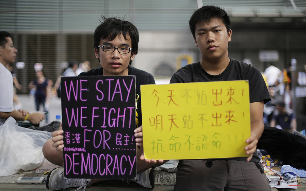 Student protesters sit with signs on their fight for democracy in Hong Kong Wednesday, Oct. 1, 2014. Holiday crowds swelled into the tens of thousands as student leaders met with other pro-democracy protesters Wednesday to thrash out a strategy for handling the government's rejection of their demands that the city's top leader resign and Beijing revise its plans to limit political reforms. (AP Photo/Wong Maye-E)