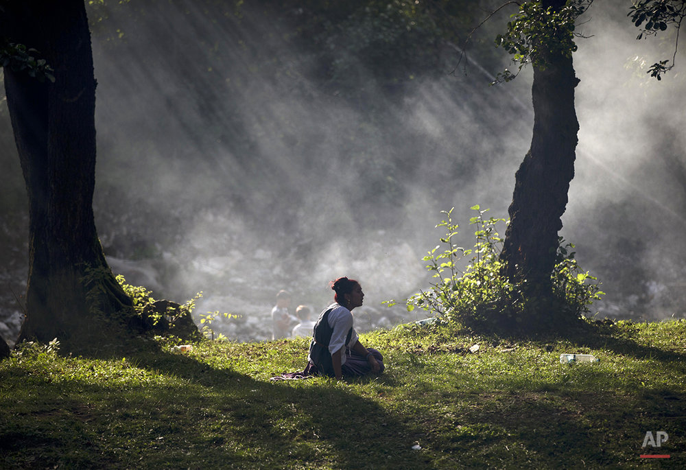 The sun rays are filtered through smoke as a Romanian Roma sits on the grass while the Roma community celebrates the Birth of the Virgin Mary in Costesti, Romania, Monday, Sept. 8, 2014. (AP Photo/Vadim Ghirda)