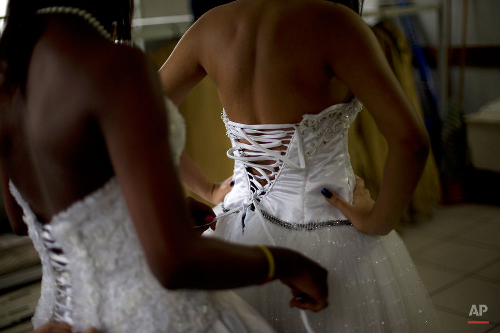 "Teenage girls from the Santa Marta ""favela"" slum prepare for their group debutante ball organized by the Pacifying Police Unit from their neighborhood in Rio de Janeiro, Brazil, Friday, Aug. 29, 2014. All of the debutantes turned 15 this year, but few had the means to celebrate the milestone with one of the lavish blowouts that are de rigueur among wealthier Brazilians. (AP Photo/Silvia Izquierdo)"