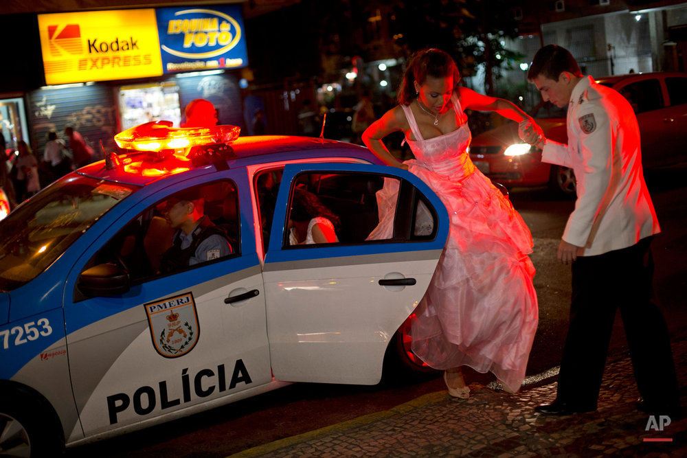 "In this Friday, Aug. 29, 2014 photo, a teenage girl from the Santa Marta ""favela"" slum exits a police car as she takes the hand of an officer who patrols her neighborhood, as she arrives to Copacabana for a group debutante ball organized by her slum's Pacifying Police Unit in Rio de Janeiro, Brazil. The ball, which relied on volunteers who coiffed and made up the girls and a formal wear shop that loaned the dresses, helped build goodwill between pacified favelas' residents and the officers who patrol them. (AP Photo/Silvia Izquierdo)"