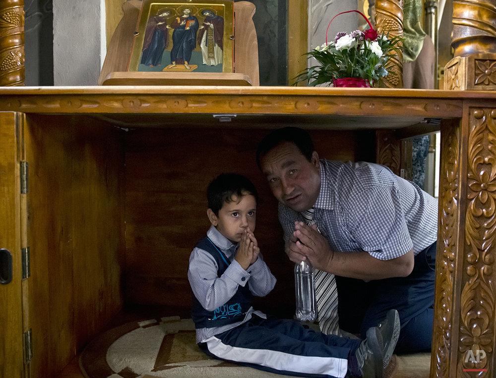Romania Religion Gypsy Virgin MA Romanian Roma man teaches his son to pray during a religious service celebrating the Birth of the Virgin Mary at the Bistrita Monastery in Costesti, Romania, Monday, Sept. 8, 2014. (AP Photo/Vadim Ghirda)ary