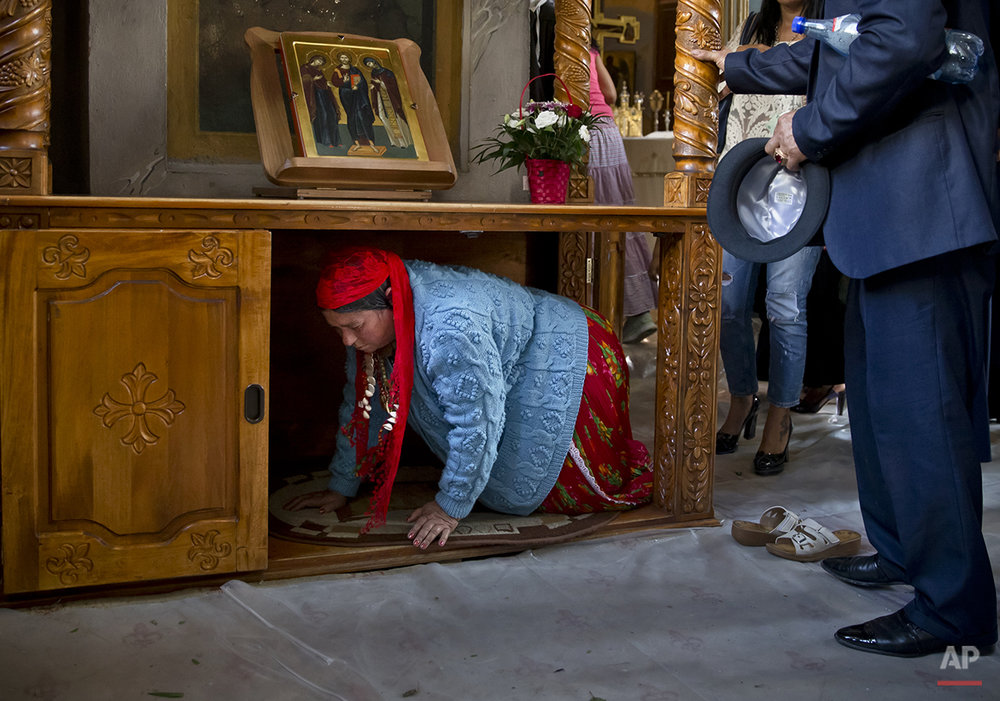 Romania Religion Gypsy Virgin MaryA Romanian Roma woman passes under a table, part of a local tradition, during a religious service celebrating the Birth of the Virgin Mary at the Bistrita Monastery in Costesti, Romania, Monday, Sept. 8, 2014. (AP Photo/Vadim Ghirda)