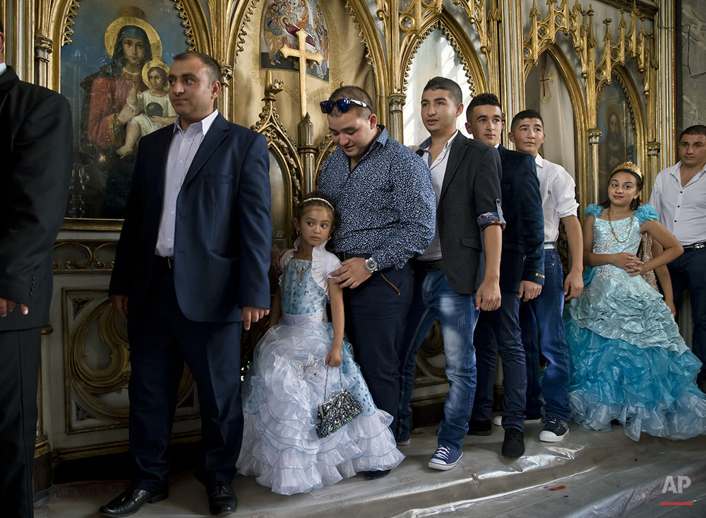Romanian Roma people pass by icons during a religious service celebrating the Birth of the Virgin Mary at the Bistrita Monastery in Costesti, Romania, Monday, Sept. 8, 2014. (AP Photo/Vadim Ghirda)
