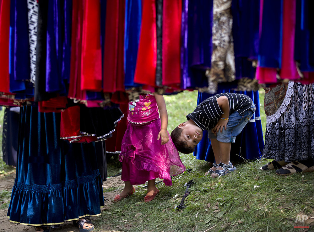 A Roma boy watches as women look at skirts while the Roma community celebrates the Birth of the Virgin Mary in Costesti, Romania, Monday, Sept. 8, 2014. (AP Photo/Vadim Ghirda)