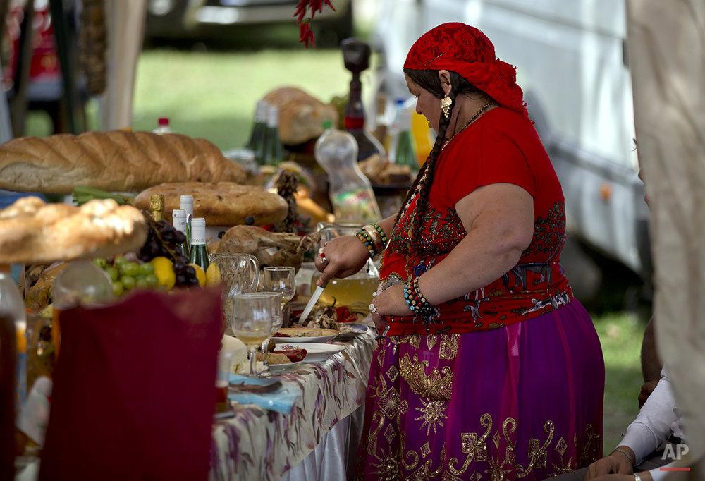 A Roma woman cuts food as the Roma community celebrates the Birth of the Virgin Mary in Costesti, Romania, Monday, Sept. 8, 2014. (AP Photo/Vadim Ghirda)