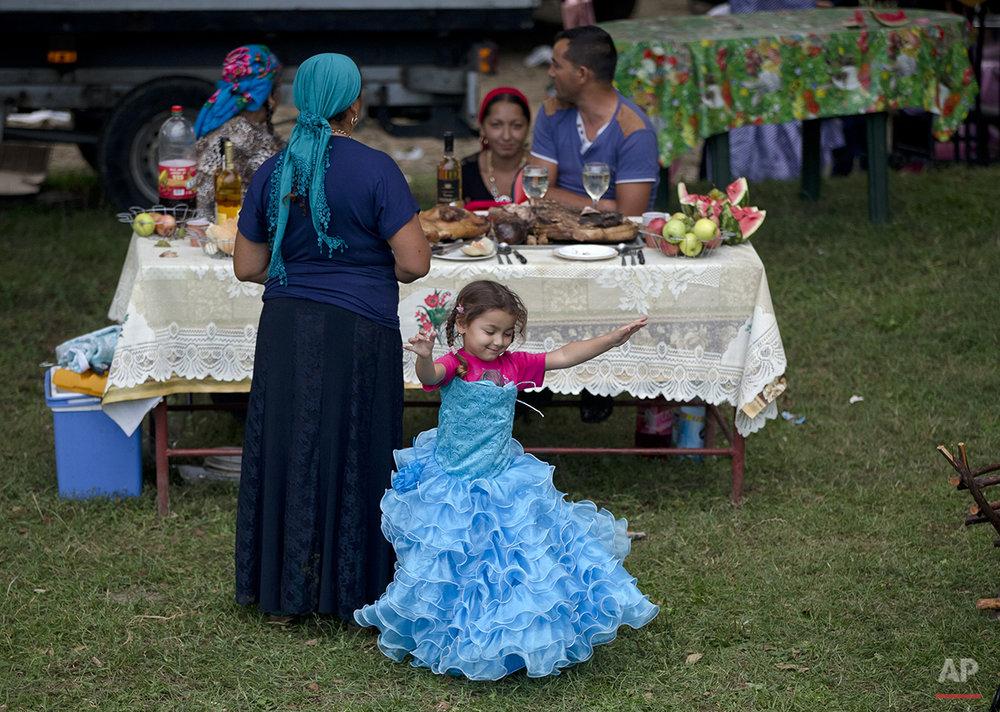 A Roma child dances as the Roma community celebrates the Birth of the Virgin Mary in Costesti, Romania, Monday, Sept. 8, 2014.(AP Photo/Vadim Ghirda)