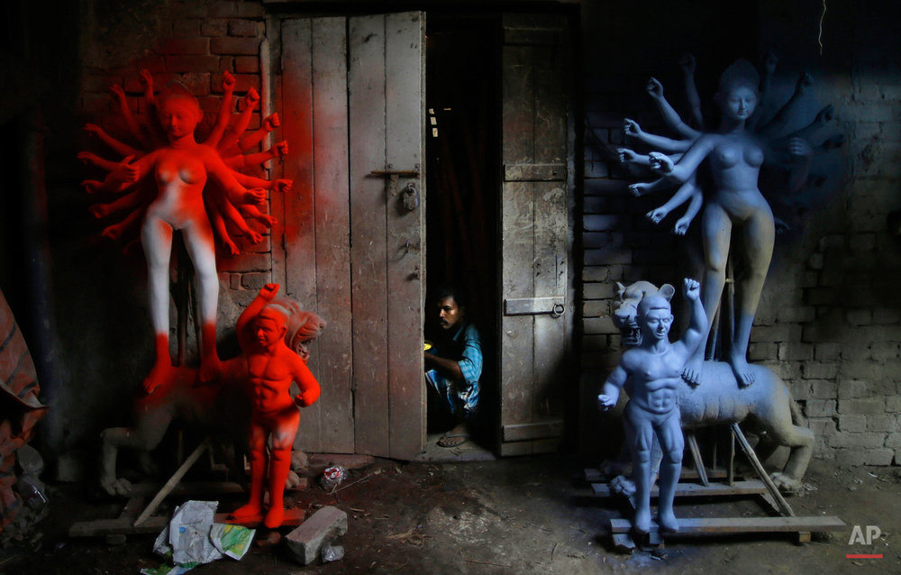 A laborer looks out of a workshop that prepares idols of goddess Durga in Kolkata, India, Tuesday, Oct. 16, 2012. Durga Puja, the festival dedicated to the worship of Goddess Durga begins on Oct. 20 and will continue until Oct. 24. (AP Photo/Saurabh Das)
