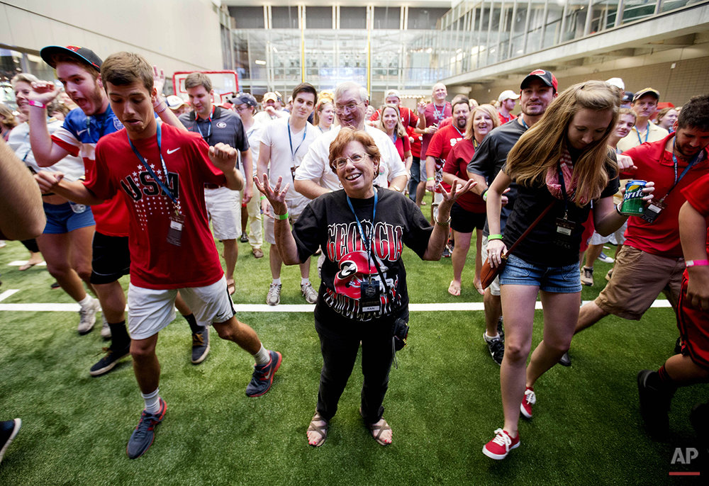 Lyn Grossman, of Smyrna Ga., throws her hands up in the air while trying to keep up with a dance move during a sleepover in the College Football Hall of Fame, Wednesday, Aug. 13, 2014, in Atlanta. Guests competed in dance competitions to win prizes before taking a tour of the museum. (AP Photo/David Goldman)
