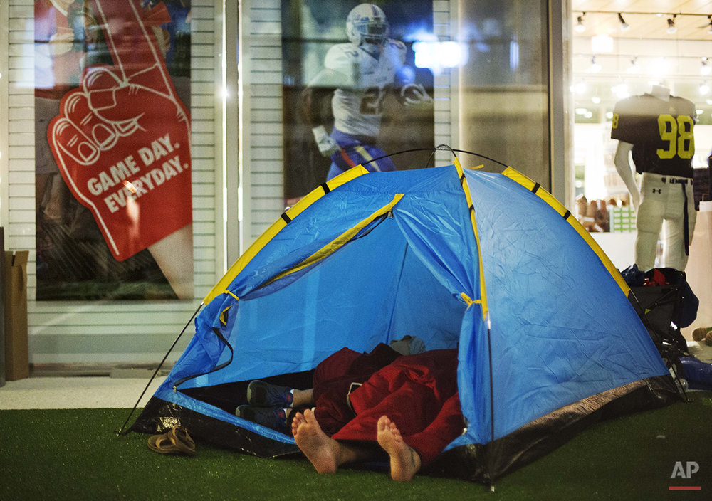 """Guests sleep in a tent next to the gift shop during a sleepover in the College Football Hall of Fame, Thursday, Aug. 14, 2014, in Atlanta. After touring the exhibits guest were served dinner on the football field before pitching their tents on the turf and settling in for the night as college football themed movies such as """"Rudy"""" were played. (AP Photo/David Goldman)"""