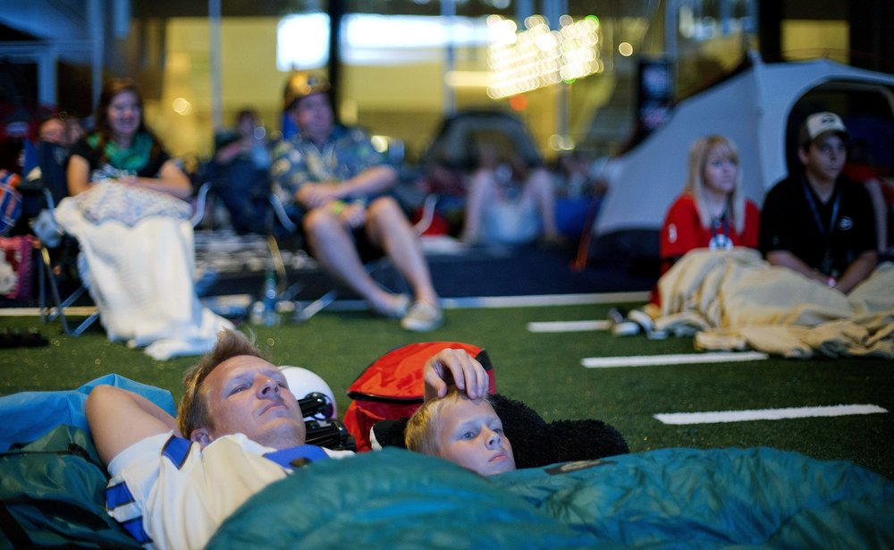 """Chip Kent and his son C.J., 9, of Suwanee, Ga., watch from their sleeping bags as the movie """"Rudy"""" is played during a sleepover in the College Football Hall of Fame just after midnight, Thursday, Aug. 14, 2014, in Atlanta. One hundred contest winners who had to write an essay detailing their love of college football were selected to stay with a guest overnight in Atlanta's College Football Hall of Fame before its grand opening and win a year's supply of Chick-fil-A. The crowd of 200 who came from as far away as Hawaii were among the first to experience the College Football Hall of Fame and Chick-fil-A Fan experience before it opens to the public on Aug. 23. After touring the exhibits guest were served dinner on the football field before pitching their tents on the turf and settling in for the night as college football themed movies such as """"Rudy""""were played on the jumbotron. The hall was previously located in South Bend, Indiana, but was plagued by poor attendance. (AP Photo/David Goldman)"""