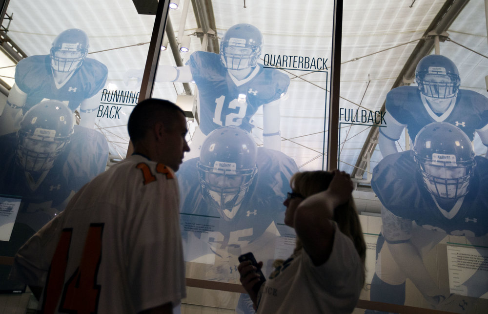 """Visitors tour the College Football Hall of Fame before spending the night, Wednesday, Aug. 13, 2014, in Atlanta. One hundred contest winners who wrote an essay detailing their love of college football were selected to stay with a guest overnight in Atlanta's College Football Hall of Fame before its grand opening and win a year's supply of Chick-fil-A. The crowd of 200 who came from as far away as Hawaii were among the first to experience the College Football Hall of Fame and Chick-fil-A Fan experience before it opens to the public on Aug. 23. After touring the exhibits guest were served dinner on the football field before pitching their tents on the turf and settling in for the night as college football themed movies such as """"Rudy""""were played on the jumbotron. The hall was previously located in South Bend, Indiana, but was plagued by poor attendance. (AP Photo/David Goldman)"""
