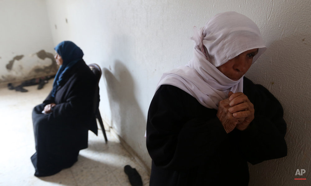 "Palestinian women mourn during the funeral of Ibrahim Suliman Mansour during his funeral in the Shajaiyeh neighborhood of Gaza City, Friday, Feb. 14, 2014. Health Ministry spokesman Ashraf al-Kidra said the 30-year-old man was shot in the head Thursday as he was collecting scrap metal near the Israeli border. He said a second man with him was shot in the back and wounded. The Israeli military said it opened fire after several Palestinians approached the border fence in northern Gaza and began ""tampering"" with the structure. It said after ""exhausting all other means"" to remove the men, it fired at the ""main instigator."" (AP Photo/Hatem Moussa)"