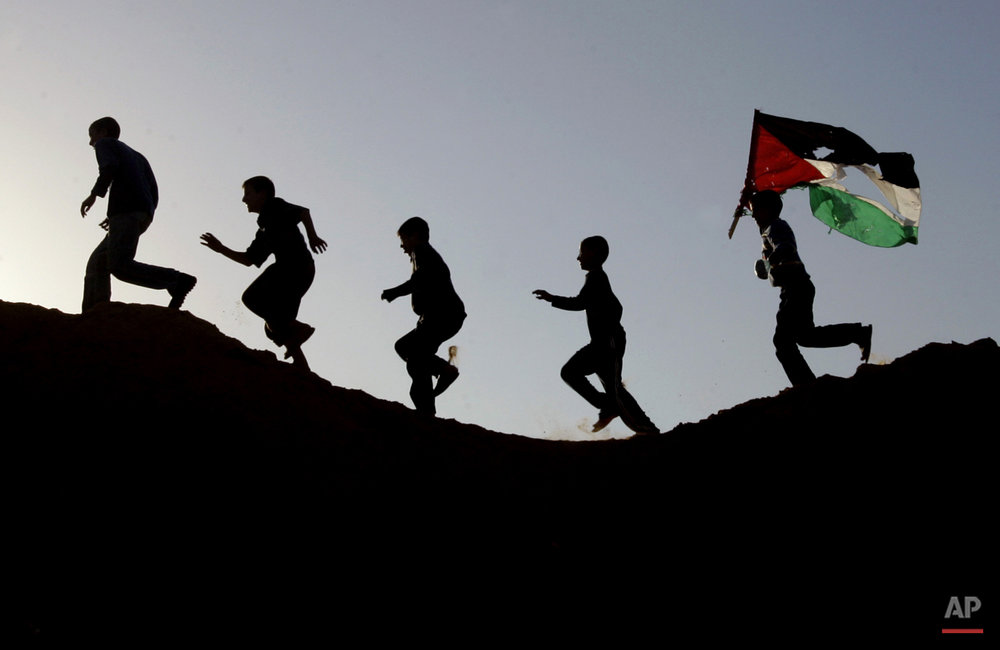 Palestinian youths, one carrying a Palestinian flag, run on a hillside after Israeli troops pulled out of Beit Lahiya, in the northern Gaza Strip, Sunday, Nov. 26, 2006. A truce meant to end five months of deadly Israeli-Palestinian clashes took hold in the Gaza Strip early Sunday, but early violations by Palestinian militants tempered hopes the accord would help to coax moribund peace talks back to life. The Israeli military said all troops were withdrawn from Gaza in the hours before the 6 a.m. cease-fire, announced late Saturday, went into effect. Dozens of tanks and armored vehicles were parked just over the border in a military staging ground in southern Israel early Sunday, and the streets of northern Gaza were empty. (AP Photo/Hatem Moussa)