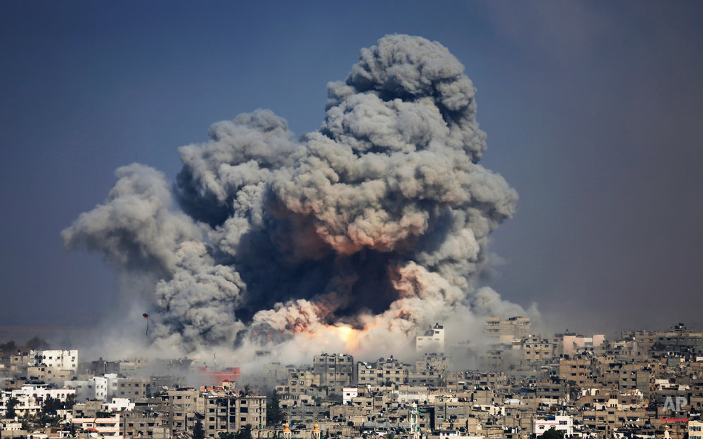 Smoke and fire from the explosion of an Israeli strike rise over Gaza City,  Tuesday, July 29, 2014. Israel escalated its military campaign against Hamas on Tuesday, striking symbols of the group's control in Gaza and firing tank shells that shut down the strip's only power plant in the heaviest bombardment in the fighting so far. The plantís shutdown was bound to lead to further serious disruptions of the flow of electricity and water to Gazaís 1.7 million people. (AP Photo/Hatem Moussa)