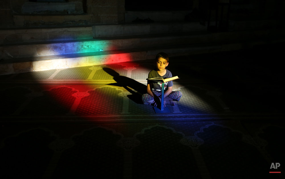 A Palestinian boy reads the Quran, Islam's holy book, in the Al-Omari mosque in Gaza City on Sunday, June 29, 2014. Muslims throughout the world are celebrating the holy fasting month of Ramadan, refraining from eating, drinking, and smoking from dawn to dusk. (AP Photo/Hatem Moussa)