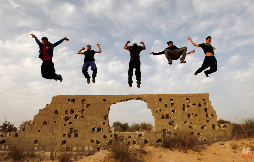 Palestinian youths practice their parkour skills in KhanYounis, southern Gaza Strip , Sunday, March 31, 2013. Parkour is a physical discipline of movement focused on overcoming obstacles. Training is held at cemeteries in KhanYounis. (AP Photo/Hatem Moussa)