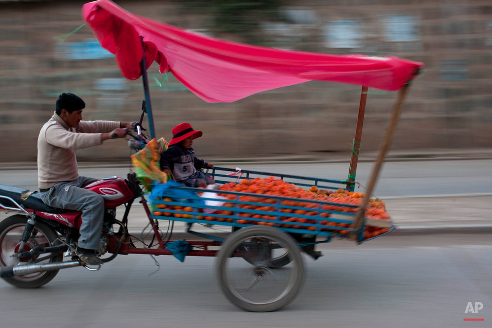 A man rides a motorcycle attached to a makeshift container that serves as a vendors' stand when stationary, in Huancavelica, Peru, Tuesday, Aug. 20, 2013. (AP Photo/Rodrigo Abd)