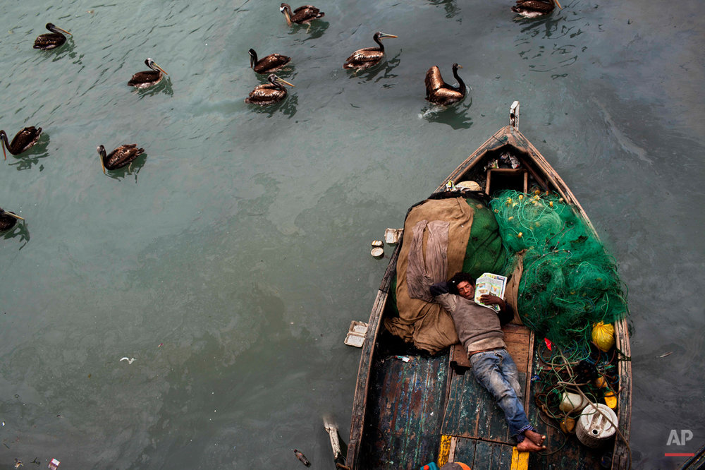 A fisherman takes a nap on his boat after deep sea fishing all night in El Callao, Peru, Nov. 3, 2012.  Small scale fishermen in this area work 24 hour shifts, catching mostly anchovy, mackerel and silverside. (AP Photo/Rodrigo Abd)